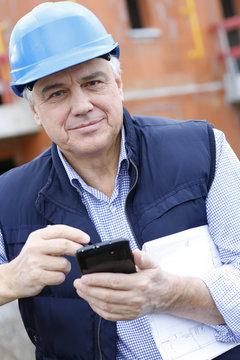 Entrepreneur on construction site using smartphone