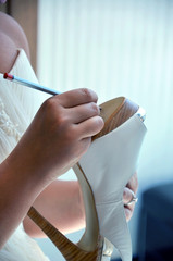 bride writing names under her shoe as a tradition before wedding