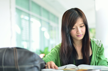 beautiful asian girl is reading in college