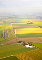 Several windmills and farm at Dutch landscape from above