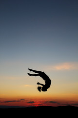 Fototapete - silhouette of female gymnast doing a somersault in sunset