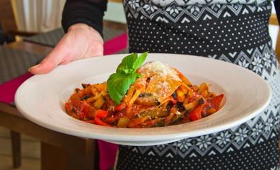 lasagna in hand of server