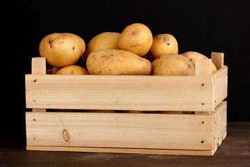 Ripe potatoes in wooden box on wooden table on black background