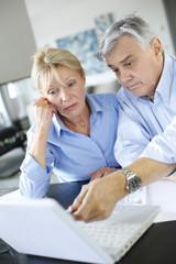 Senior couple inquiring bank website for help