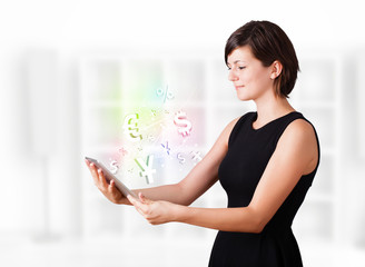 Young woman looking at modern tablet with currency icons