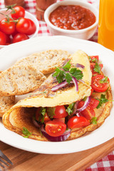 Classic omelete with toasted bread and cherry tomato