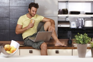 Young man with laptop and sandwich