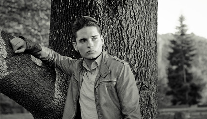 Attractive young male model leaning on tree