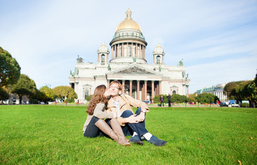 Joyful couple sitting on the grass near St. Isaac's cathedral an