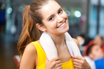 Fitness woman with towel around her neck
