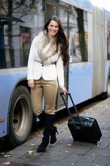Fröhliche junge Frau an der Bushaltestelle
