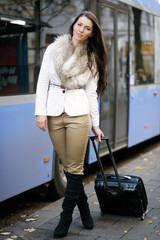 Hübsche dunkelhaarige Frau an der Bushaltestelle