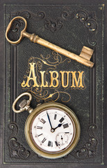 vintage album with ild key and clock