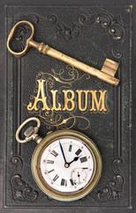 vintage album with ild key and clock