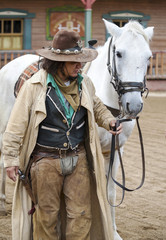 Fotomurales - Cowboy standing next to his horse at Mini Hollywood,Spain