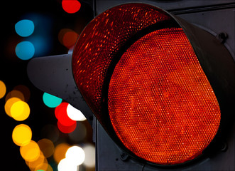 Red traffic light with colorful unfocused lights on a background