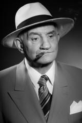 Senior vintage man wearing hat. Black and white shot. Gangster.