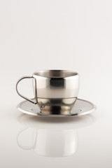 metal cup and saucer on white