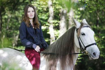 junges mädchen reitet auf weißem pferd im wald