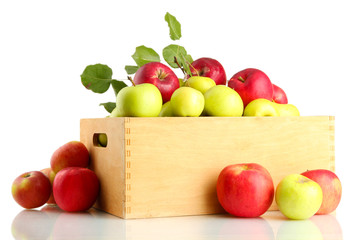 juicy apples with green leaves in wooden crate, isolated