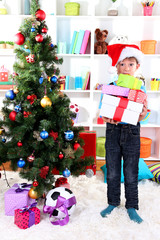 Little boy in Santa hat stands near Christmas tree with gifts