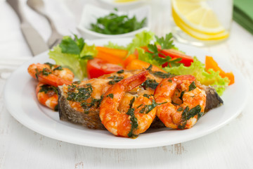 fish with shrimps and salad on the plate and glass of water