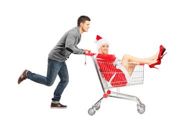 Guy pushing a woman wearing christmas costume in a shopping cart