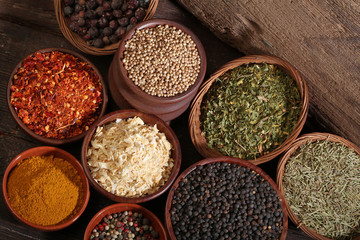 Different bowls of spices over a wooden background