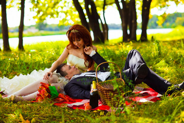 in Russia couple bride and groom communicate sitting on green gr