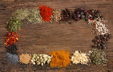 Different spices over a wooden background.