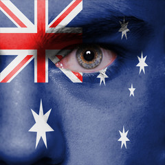 Man with the flag of the Australia painted on face.