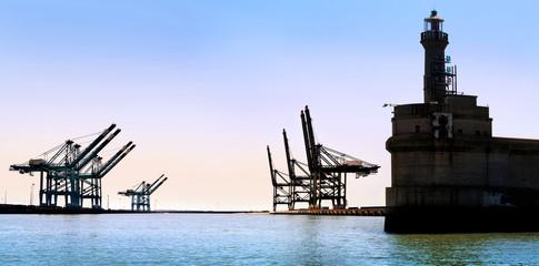 Cargo sea port. Old lighthouse. Sea cargo cranes.