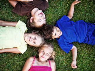 Portrait of childrens posing on grass and smiling