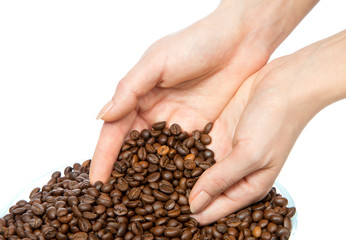 coffee beans pouring out of cupped woman hands