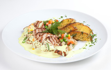 Fried potatoes with meat and grilled vegetables laid out on a pl