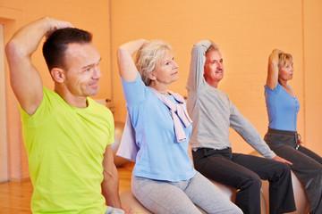 Senioren dehnen sich im Fitnesscenter