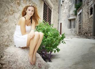 Woman sitting barefoot on street