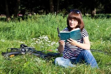 Девушка в очках читает книгу в парке