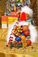 Christmas hat with gift boxes, baubles on christmas tree backgr