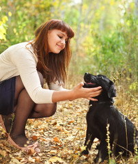 Teenager girl with black labrador retriever puppy