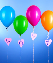 Colorful balloons keeps word love on blue background
