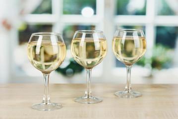 White wine in glass on window background