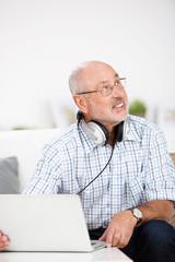 älterer mann mit kopfhörern und laptop