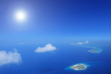 Sun and clouds over islands in Laccadives sea, Maldives