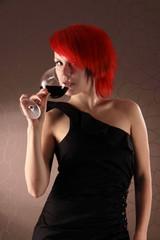 Schlanke rothaarige Frau mit Rotwein