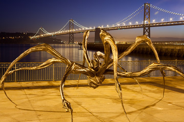 Bay Bridge with  Spider Sculpture at night. San Francisco