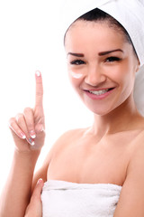 Beautiful and young woman applying cream on a face