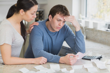 Worried couple looking over bills