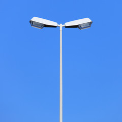 Double street lamp post on blue sky background