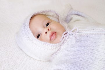 Portrait of baby in a knitted suit with a hood (2 months)